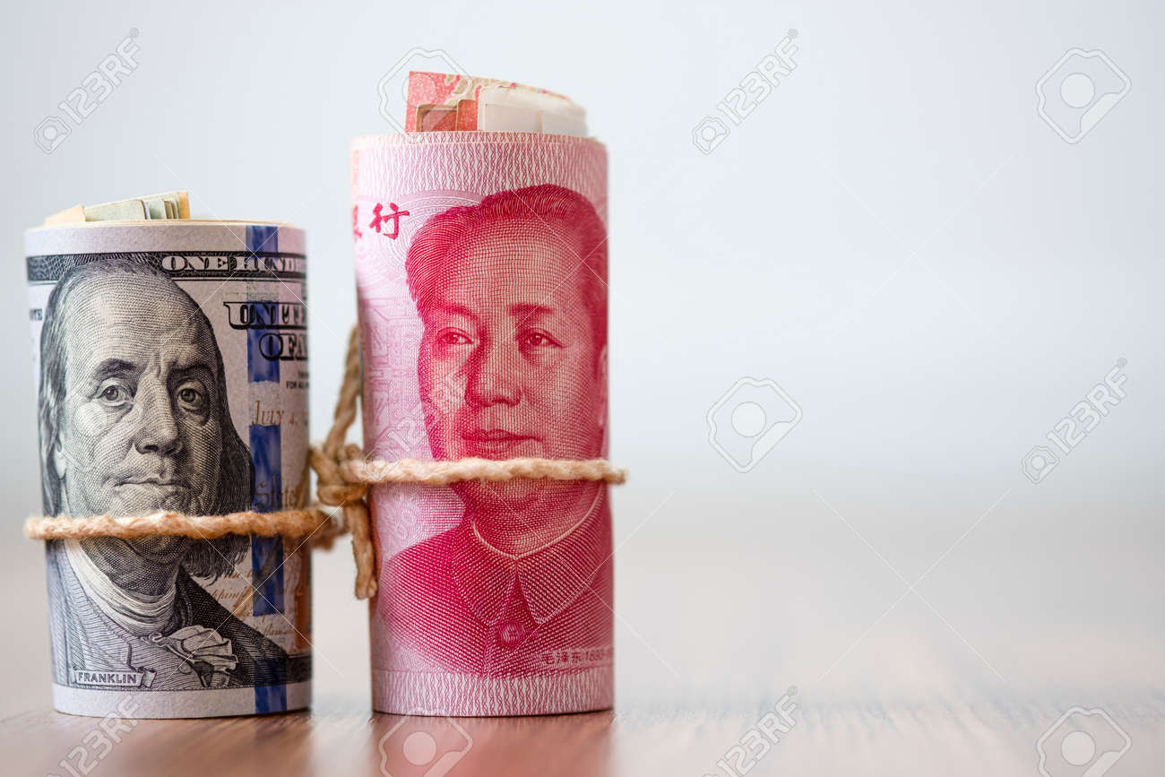 US dollar and Yuan banknote on wooden table. Its is symbol for tariff trade crisis between United States of America and China which the biggest economic country in the world. - 130027644