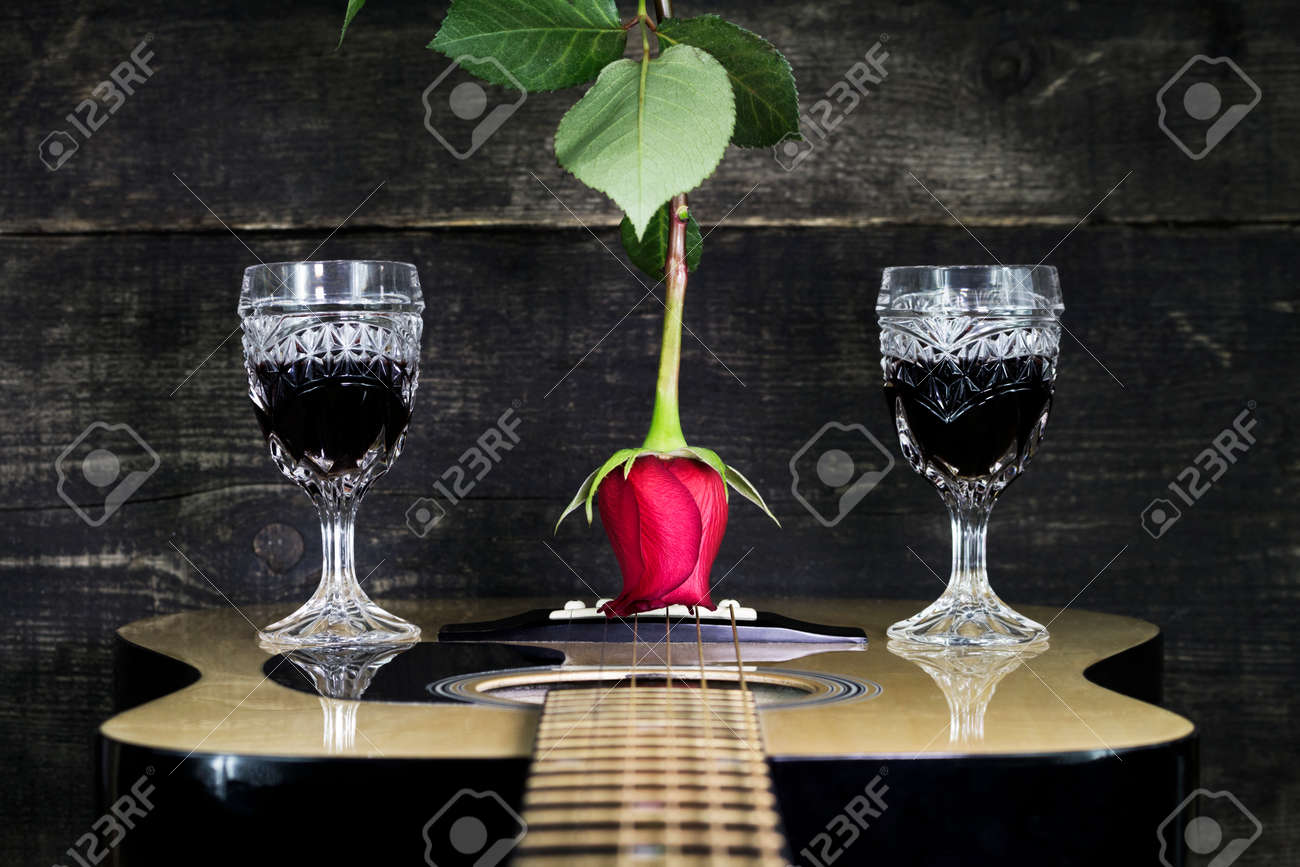 Red Rose And Wine Glasses Resting On Acoustic Guitar With Wooden Background Stock Photo