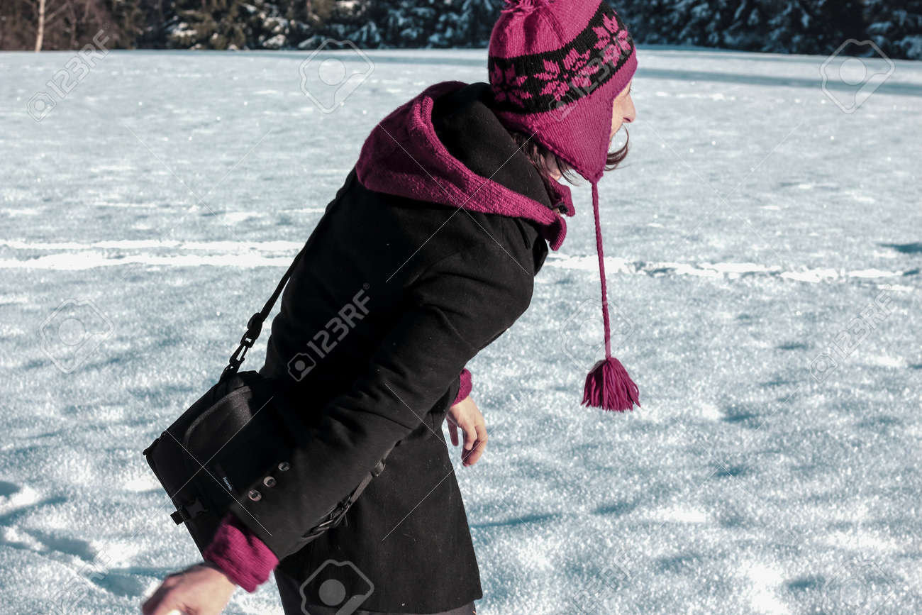 young man in warm clothing having a good time with snow in the winter - 87799072