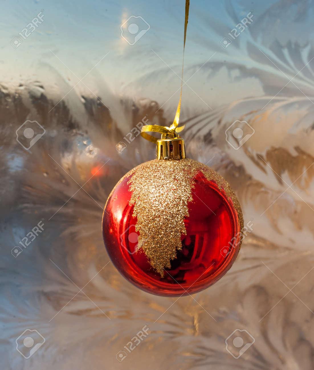 Boule De Noël Rouge Sur Le Fond De Windows Givré Banque D'Images