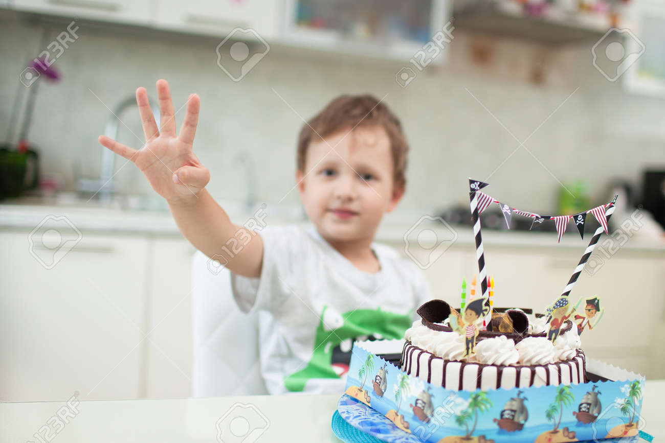 The boy sits with the cake at the table and shows how old he was - 64184107