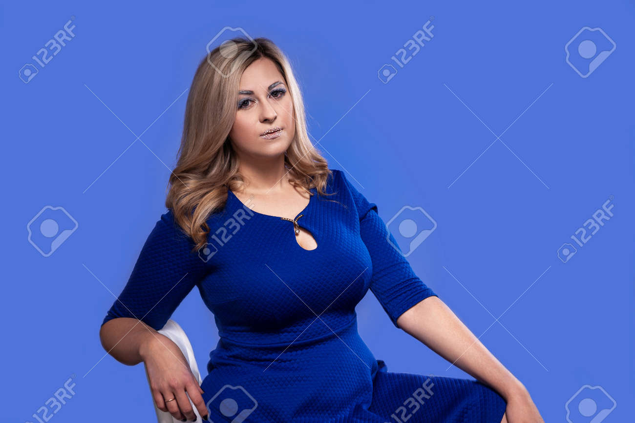 curvy blonde model with huge Breasts in Studio on blue background - 121352959