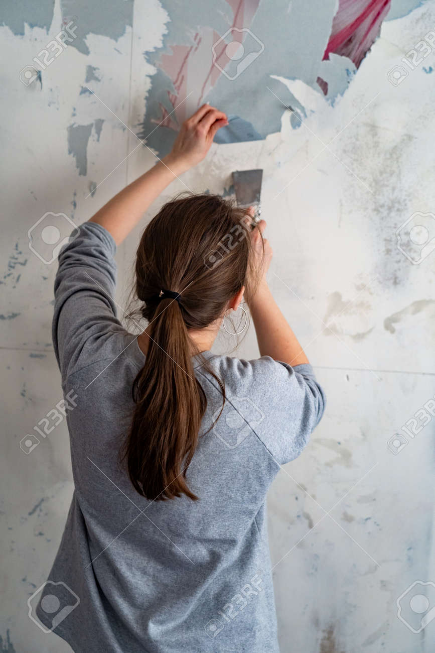 woman removes scraps of old Wallpaper from the wall with a spatula. Repair of premises. Removing wet Wallpaper. Deleting Wall paper - 145843051
