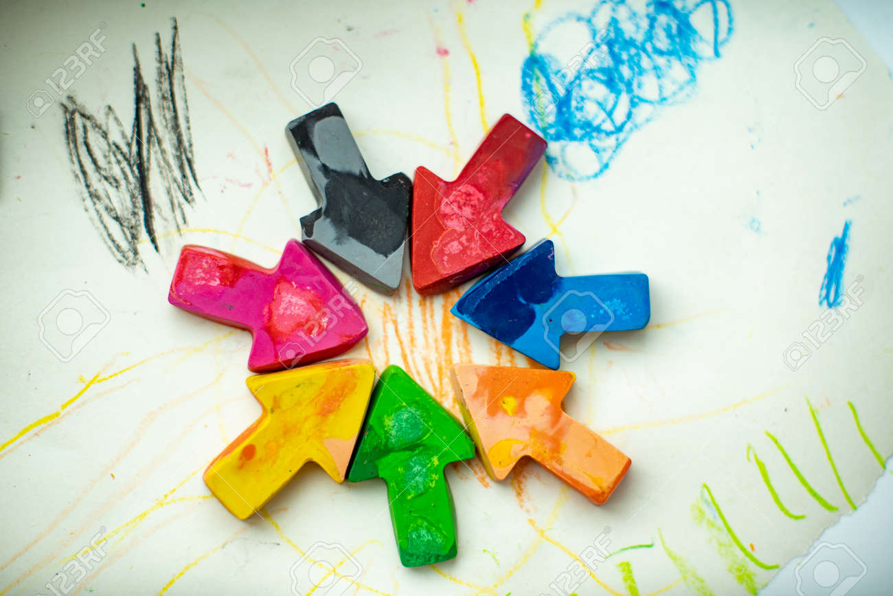 made homemade wax pencils from the wreckage of old crayons by melting them in the oven at high temperature in silicone form. crayons in the form of arrows lie on paper - 145843071