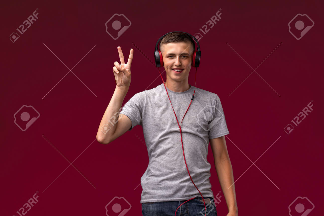 positive guy is a teenager with headphones, listening to music from his smartphone on a red background, showing a victory sign with his fingers. - 145843999