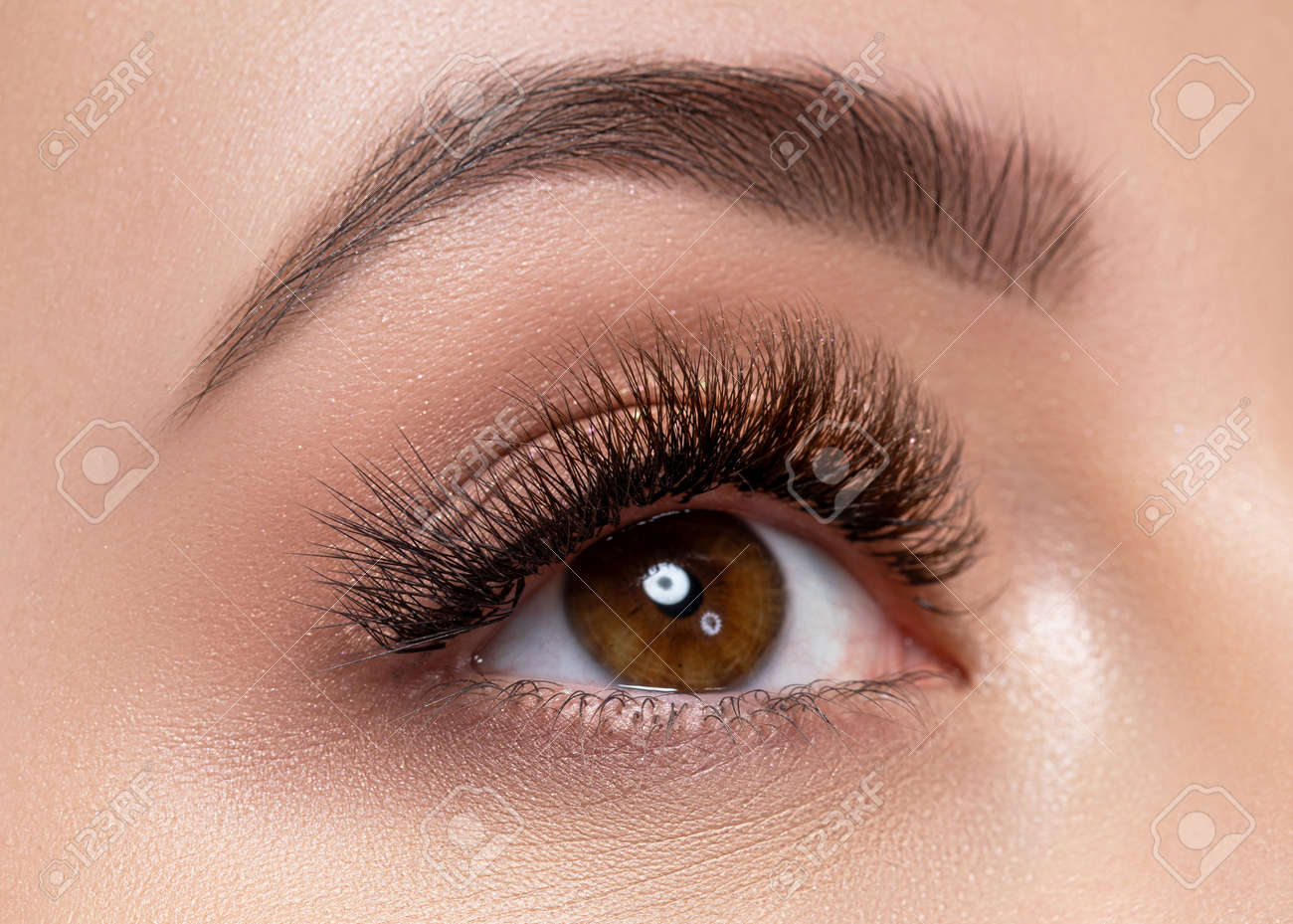 Beautiful macro photography of a woman's eye with extreme makeup of long lashes. Perfect long lashes, imitation. Rejection of cosmetics. Close-up fashion eye makeup, eyebrow lamination is beautiful - 145844000