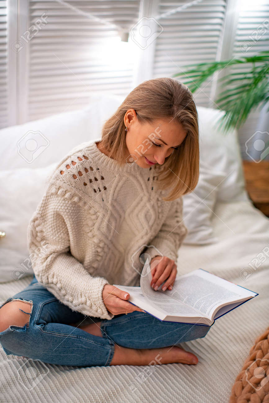young smiling woman is sitting on the bed with a book. The blonde spends time studying educational literature. The evening reading. The concept of leisure. Stay at home - 145717931