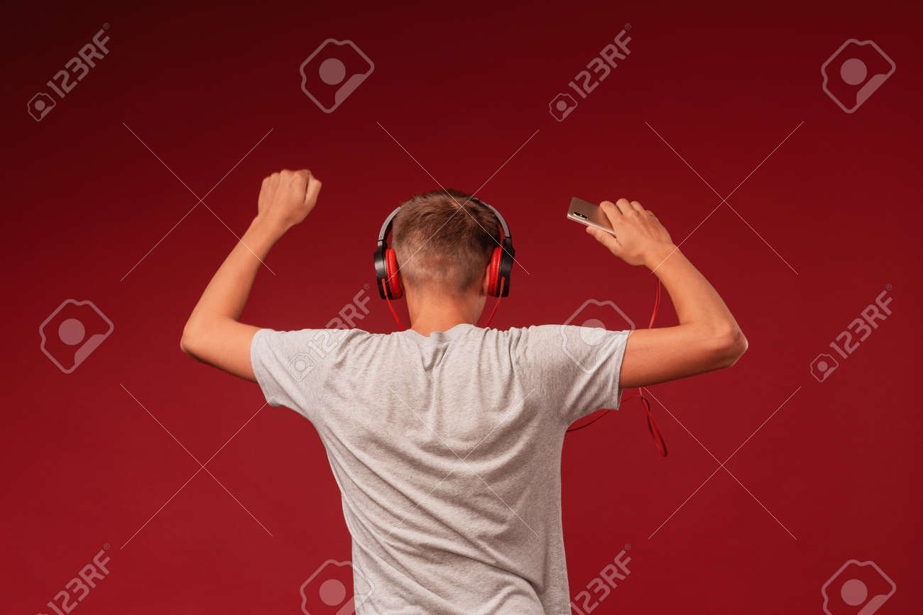 a positive teenage guy with headphones, listening to music from his smartphone on a red background, dancing with his hands up, turning his back. Rear view. - 146984443