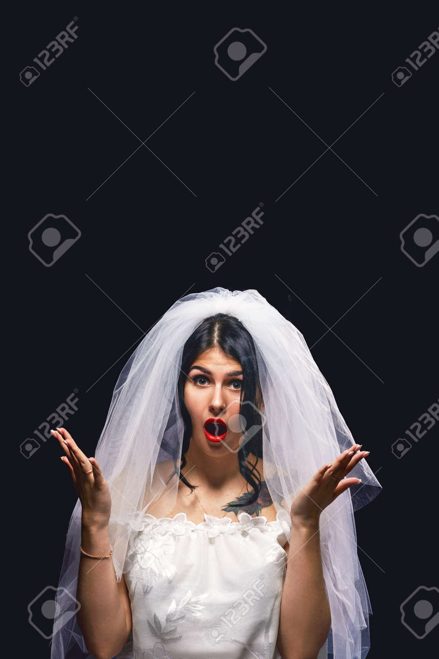 woman dressed as a bride throws a bouquet up on a black background. The brunette is very surprised that the bouquet falls on her head. Concept of wedding customs. - 145986485