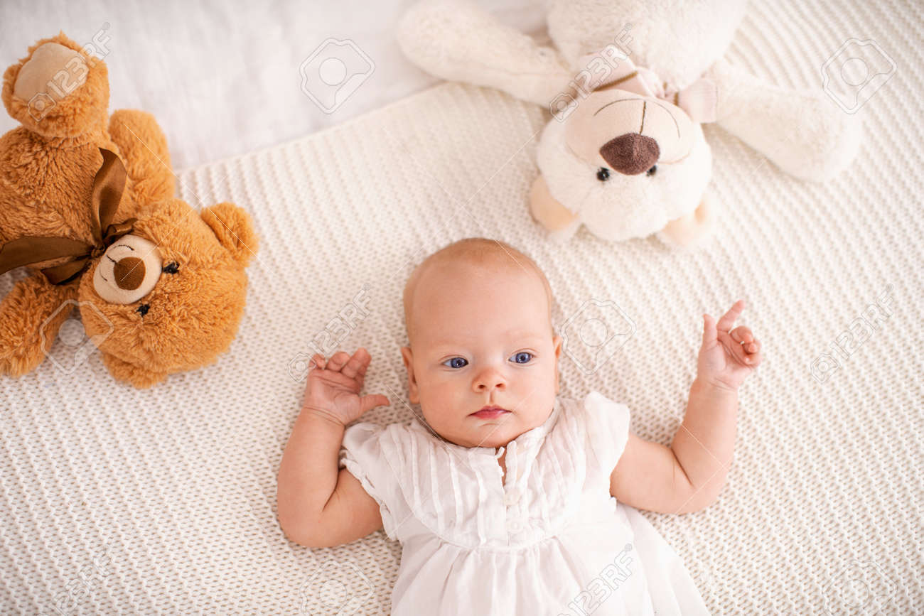 Cute little girl with blue eyes 4 months old lies on bed with Teddy bears and looks away. small curious funny baby in light clothes, watching what is happening, looking away. The view from the top. - 145987727