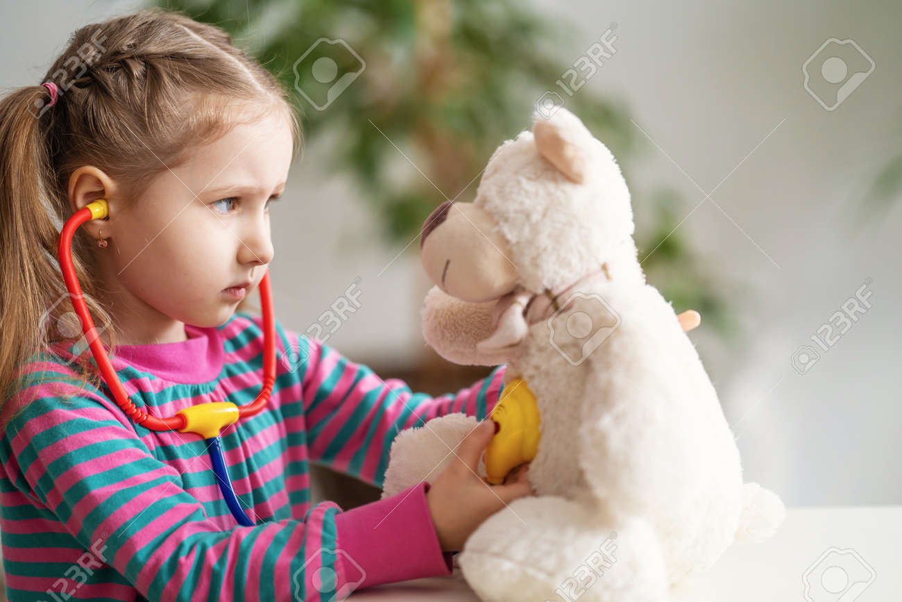 Attentive adorable small girl wearing in everyday clothes, using stethoscope on teddy bear. Attractive little preschooler playing doctor patient game in clinic, children healthcare concept. Treatment. - 145987813