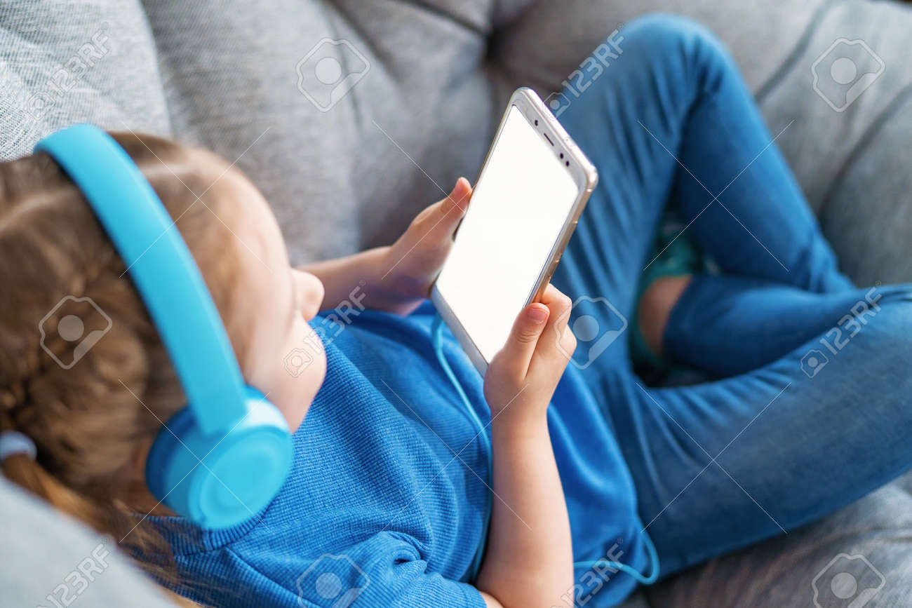 little girl with headphones and holding smartphone white screen in her hands is lying on sofa and looking at mobile phone screen. Close up. Selective focus on hand. Concept leisure during quarantine - 146984505