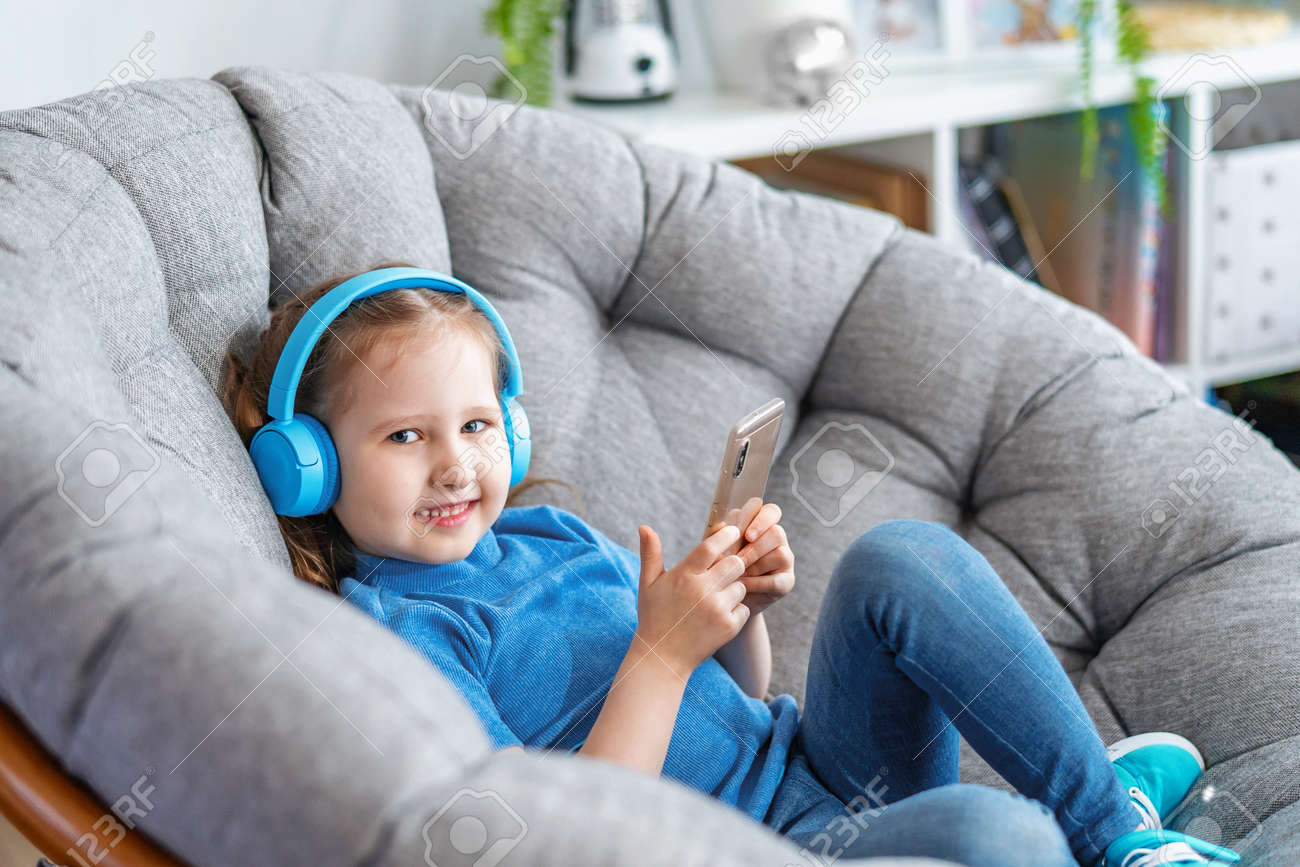 little girl with headphones and holding smartphone in her hands lies on large round armchair and looks at screen frame and smiles listens to music. Side view leisure Concept during covid-19 quarantine - 146984508