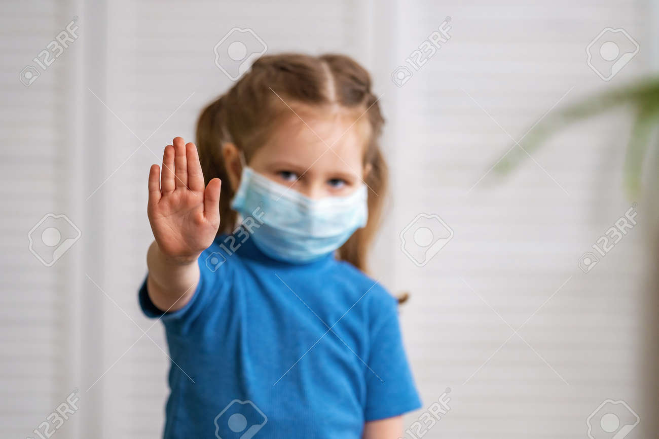 A little girl in a medical mask looks at the camera and makes a stop gesture during the coronavirus pandemic on a light background. The child puts his hand forward to determine the social distance. - 146984510