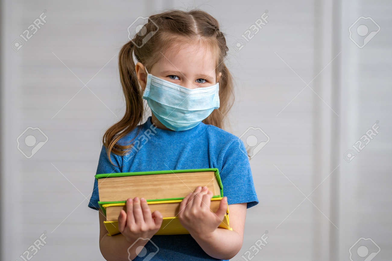 Little girl in a medical mask with a book in her hands on a light background. Education concept with copy space. during quarantine and self- isolation. e-learning due to Covid-19 coronavirus pandemic. - 146984512