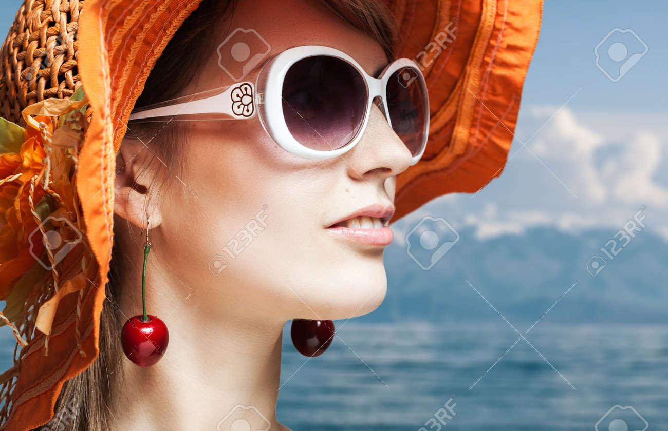 beautiful girl in orange hat and sunglasses on seaside Stock Photo - 13378649