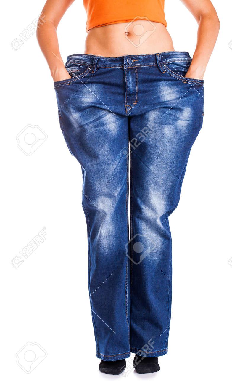 0fa6b705e7b Foto de archivo - Muchacha delgada en pantalones vaqueros grandes aislados  en blanco