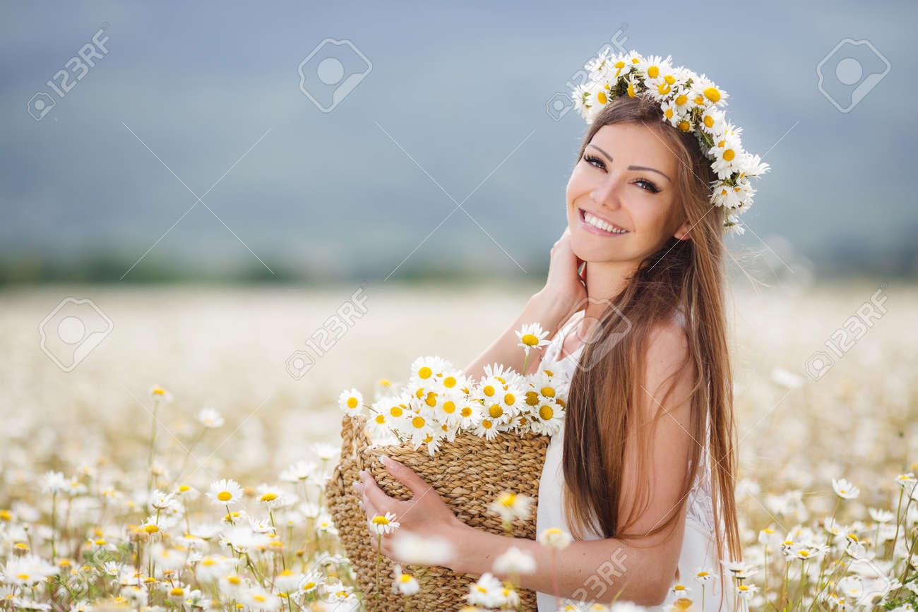 Beautiful woman enjoying daisy field - 28910636