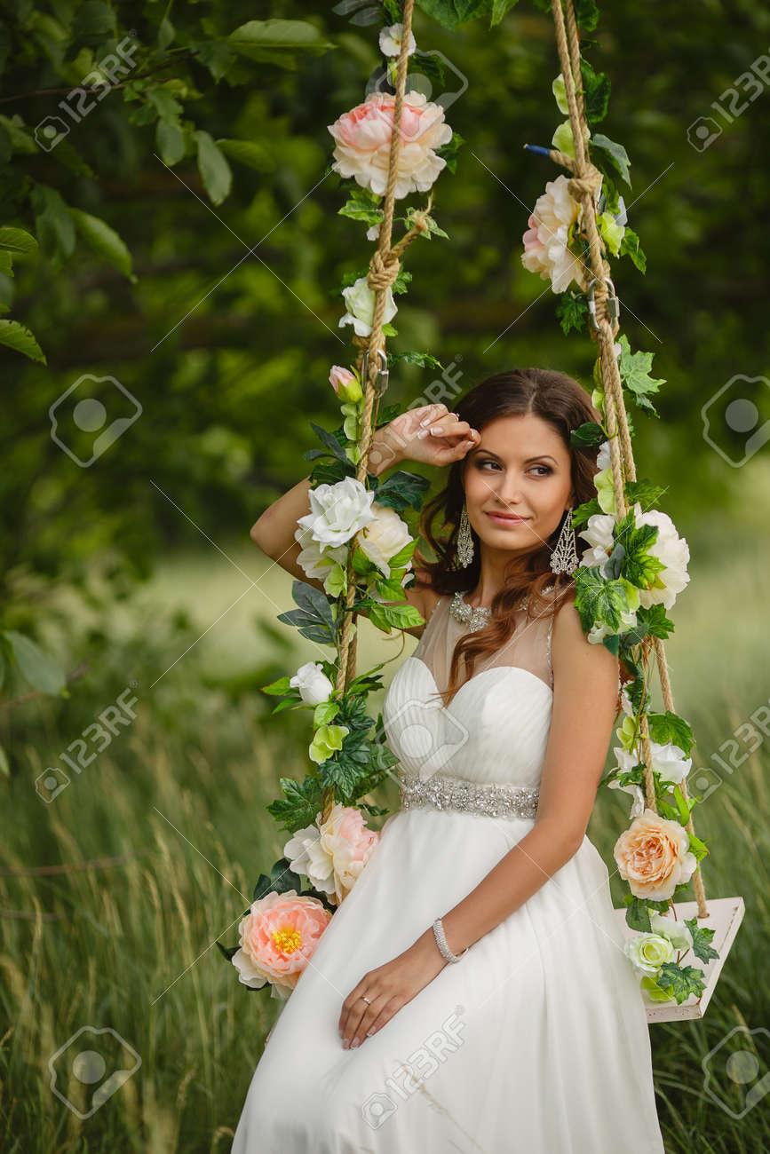 Portrait De La Belle Mariee Dans La Robe De Mariage Blanc Assis Sur Une Balancoire En Plein Air Dans Le Parc Vert En Ete