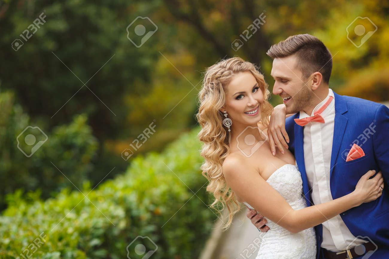 la novia y el novio en el día de la boda caminando al aire libre en