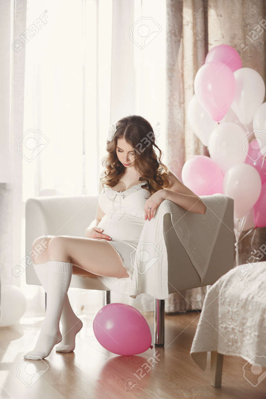 4192c1b041 Pregnant woman in a white nightgown with balloons. Beautiful young pregnant  woman in a white night shirt and white socks