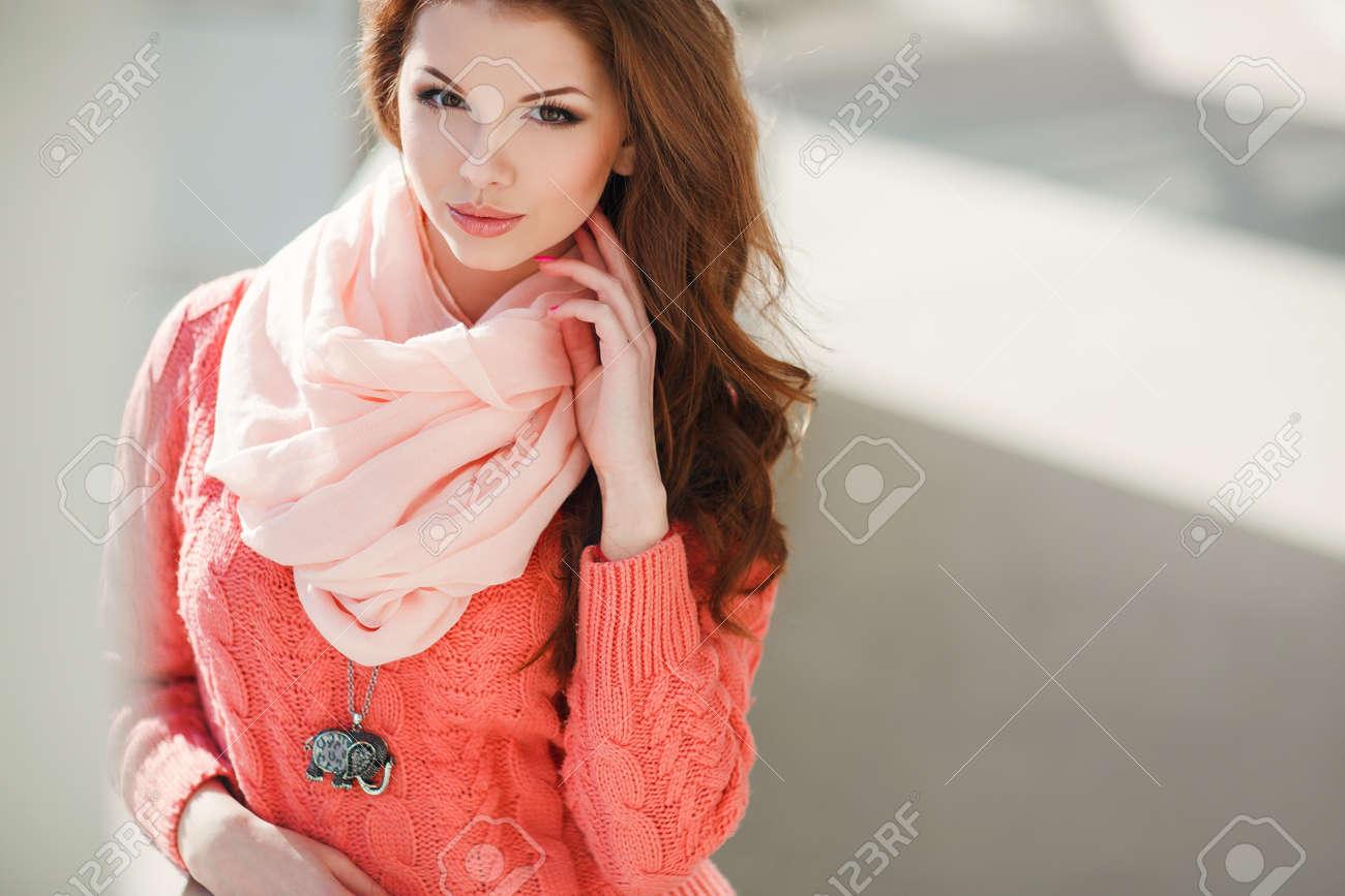 Portrait D une Belle Jeune Femme à La Châtaigne De Cheveux Longs, Yeux  Noisette Et La Lumière Maquillage, Porter Un Pull Rose Tricoté Et Une  écharpe Rose ... f453aed3dc9