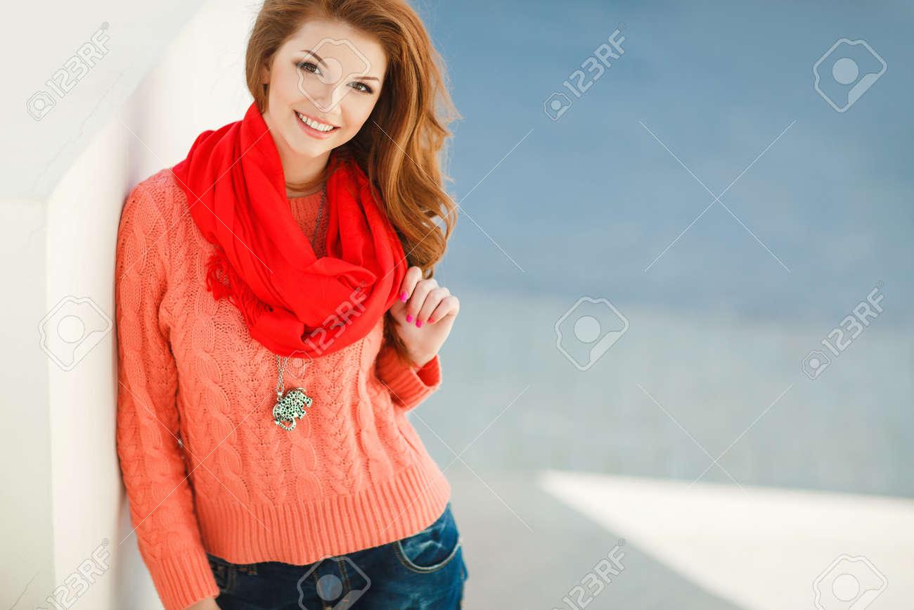 Portrait D une Belle Jeune Femme à La Châtaigne De Cheveux Longs, Yeux  Noisette Et La Lumière Maquillage, Vêtue D une Veste Rose Tricoté Et écharpe  Rouge ... 90d2bbfdc02
