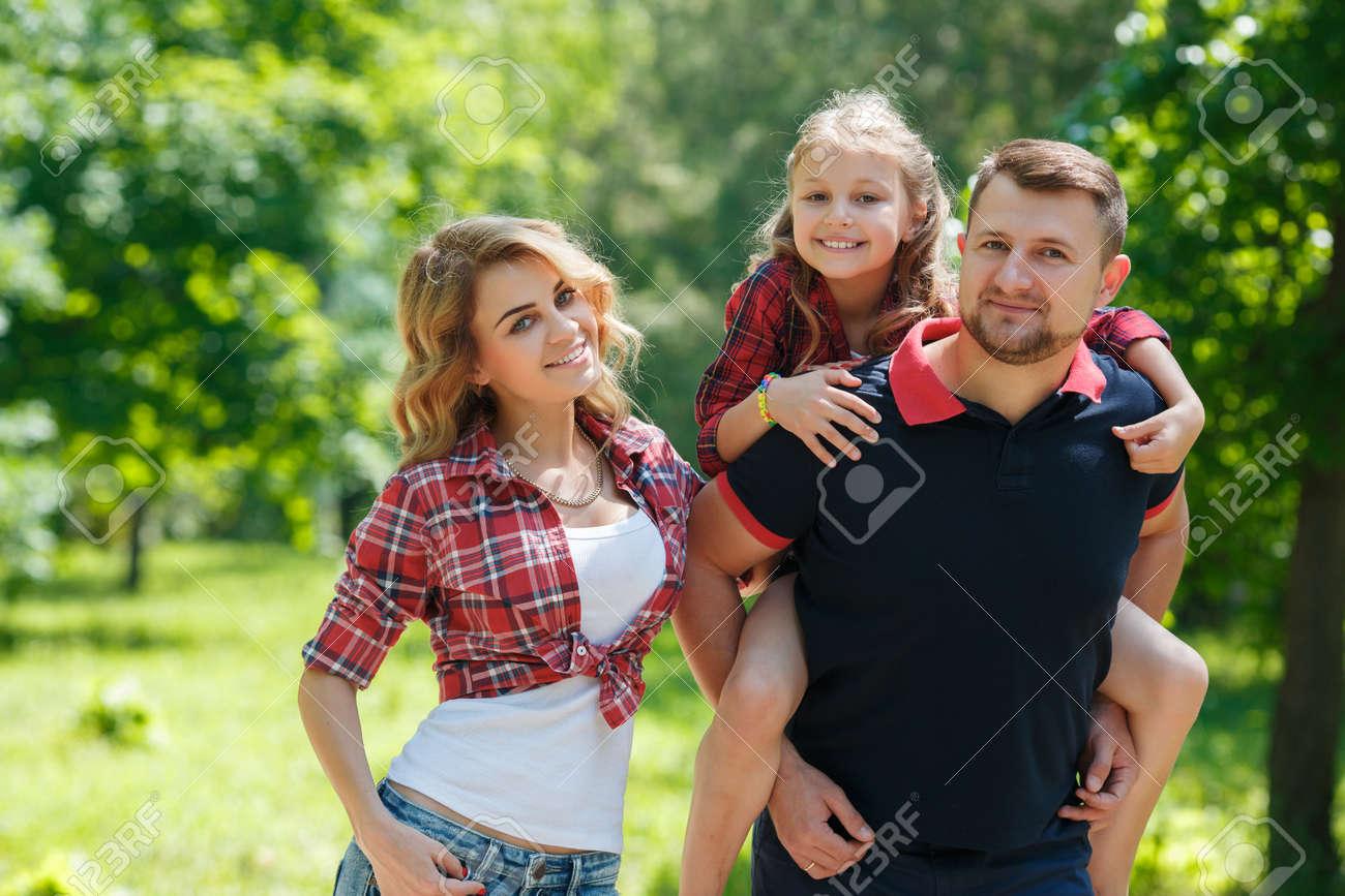 Feliz Familia Joven Pasar Tiempo Al Aire Libre En Un Día De Verano. Familia  En El Parque Juntos En Un Día Soleado. Los Padres Y La Muchacha Se Ven  Felices Y ... ee1ec3828625