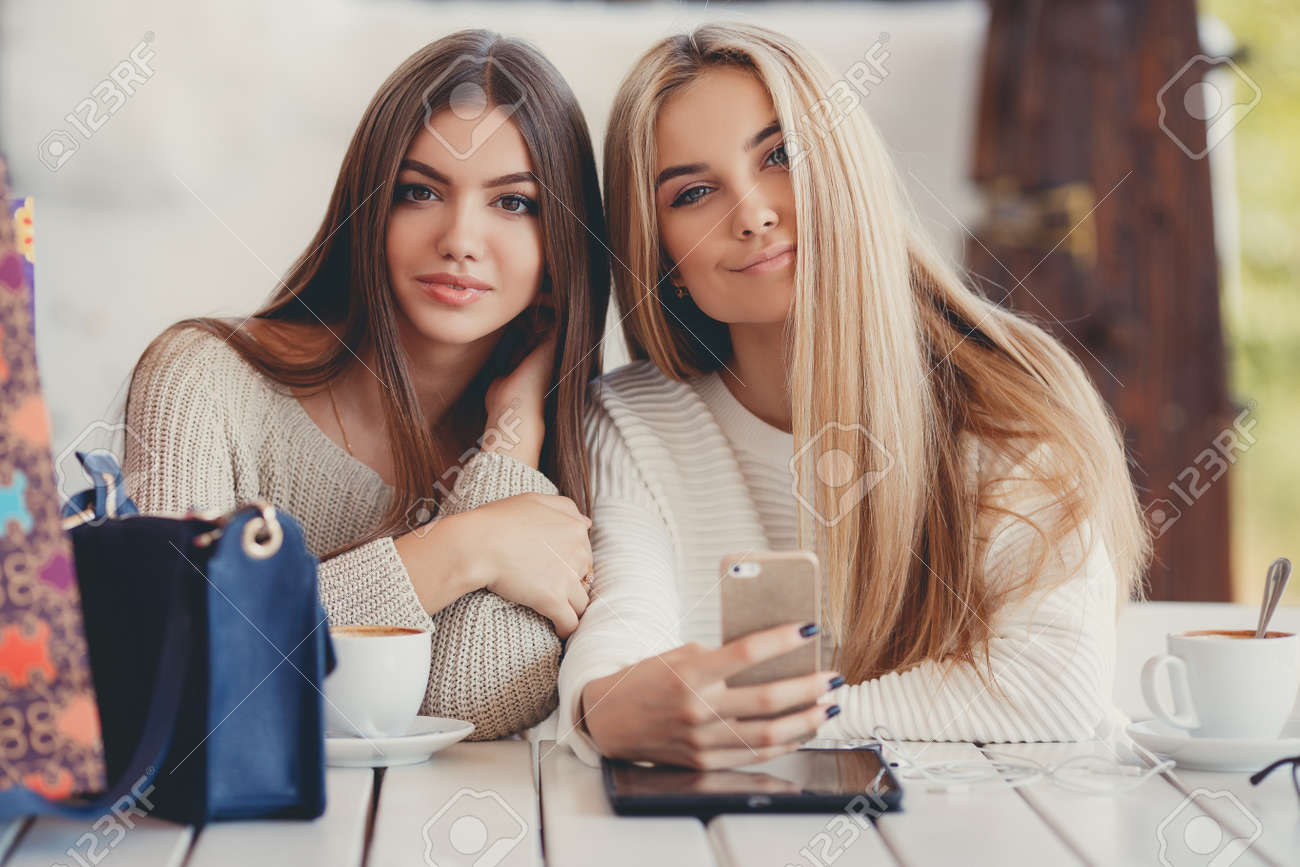 7480f689 Two young beautiful women, good friends, a blonde and a brunette, with long  straight hair, dressed in knitted light sweater, sitting at a table in a  cafe, ...