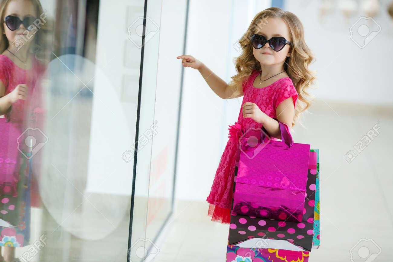 6b723261c69a Ein Schönes Kleines Mädchen Im Vorschulalter, Eine Brünette Mit Dem  Lockigen Haar, Rosa Sommerkleid, Bunten Papier-Taschen, Sonnenbrillen, Mit  Einem Süßen ...