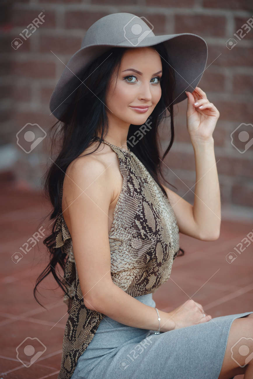 Fashionable girl in hat outdoor.Summer portrait of a beautiful woman with  long black hair f6e9e80851c7