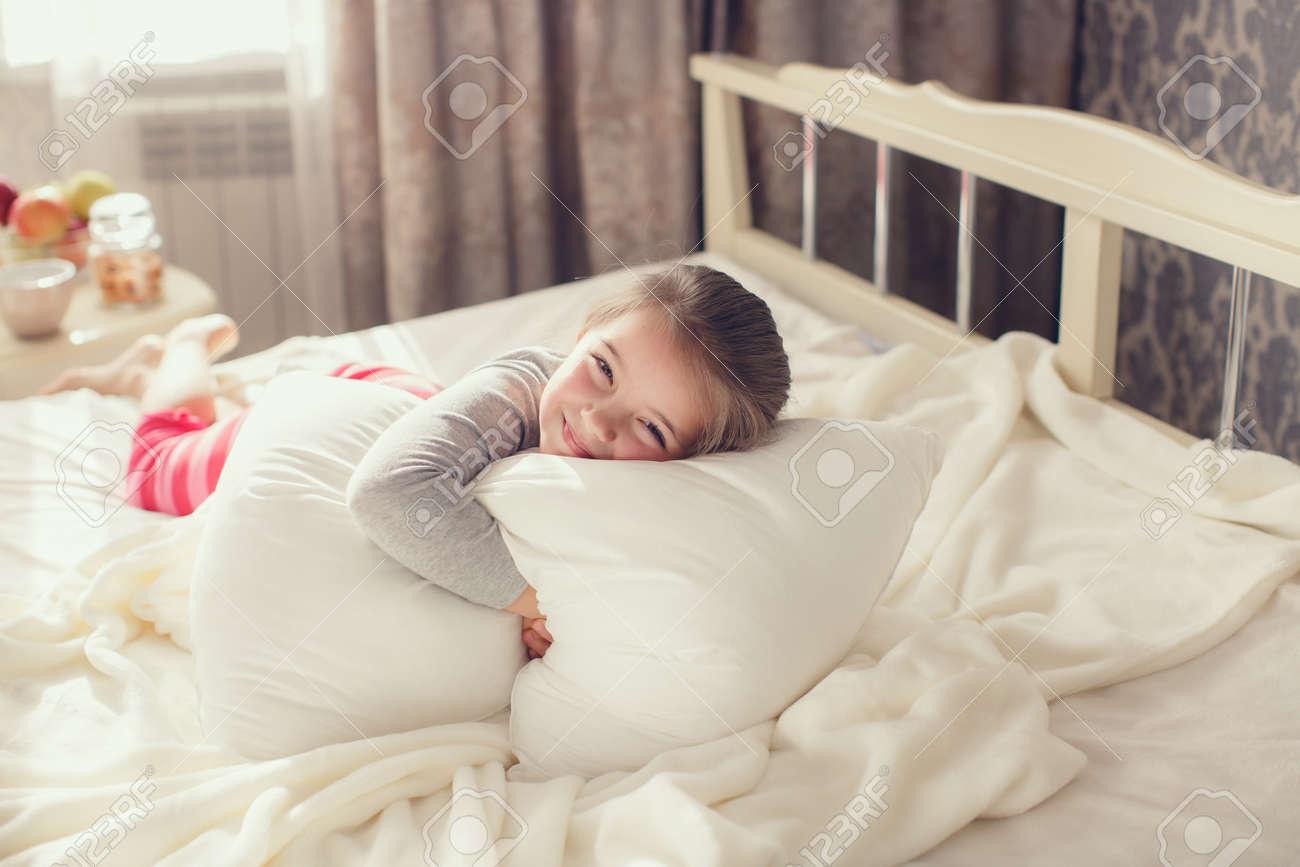 Petite fille, brune dans un rose pantalon rayé de pyjama et un T-shirt  gris, se réveille le matin sur un lit blanc dans sa chambre près de la  fenêtre, ...
