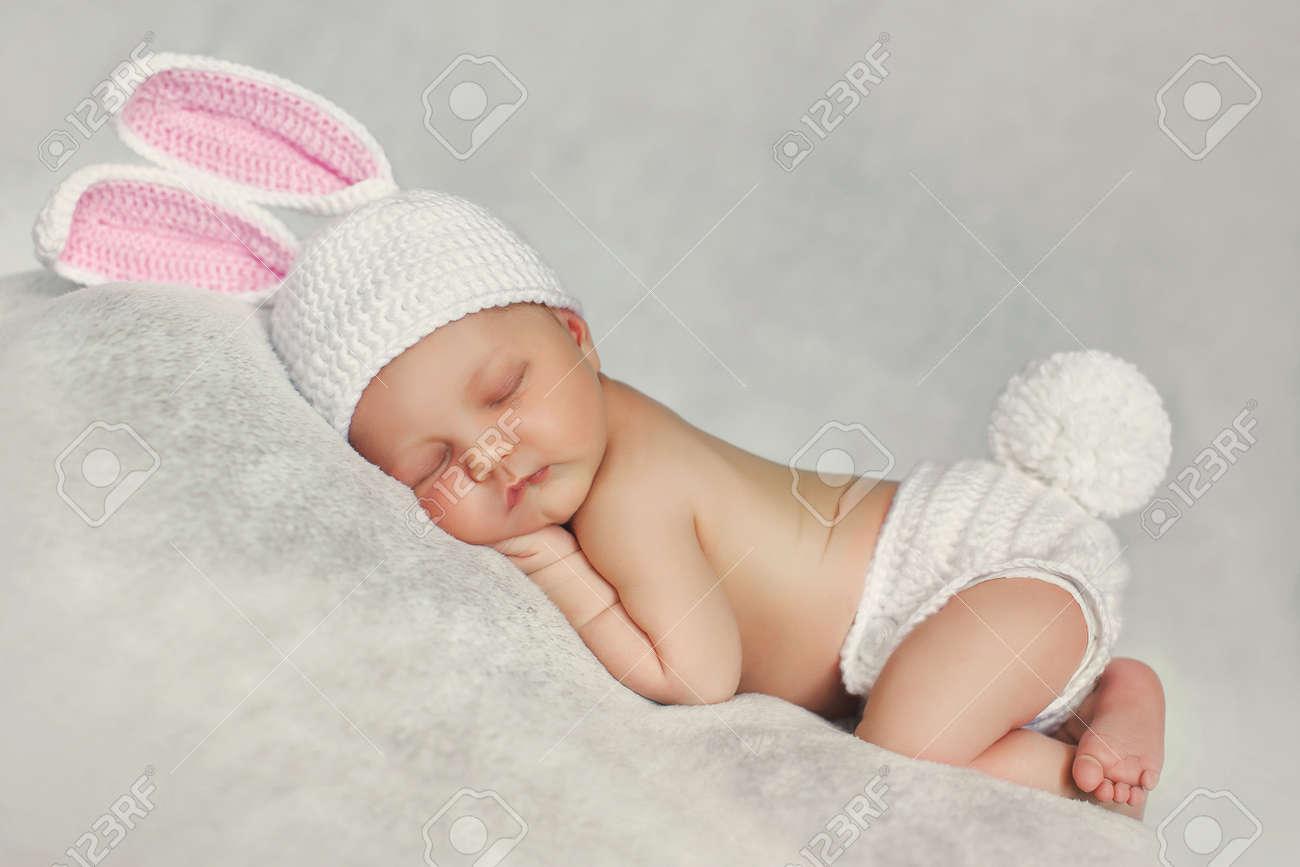 Beau Bébé Dans Un Bonnet Tricoté Blanc Avec Des Oreilles De Lapin Rose,  Blanc Culotte En Tricot Avec Une Queue De Lapin Ronde Entre Ses Jambes  Petits Pieds, ... b19a29ed1c6