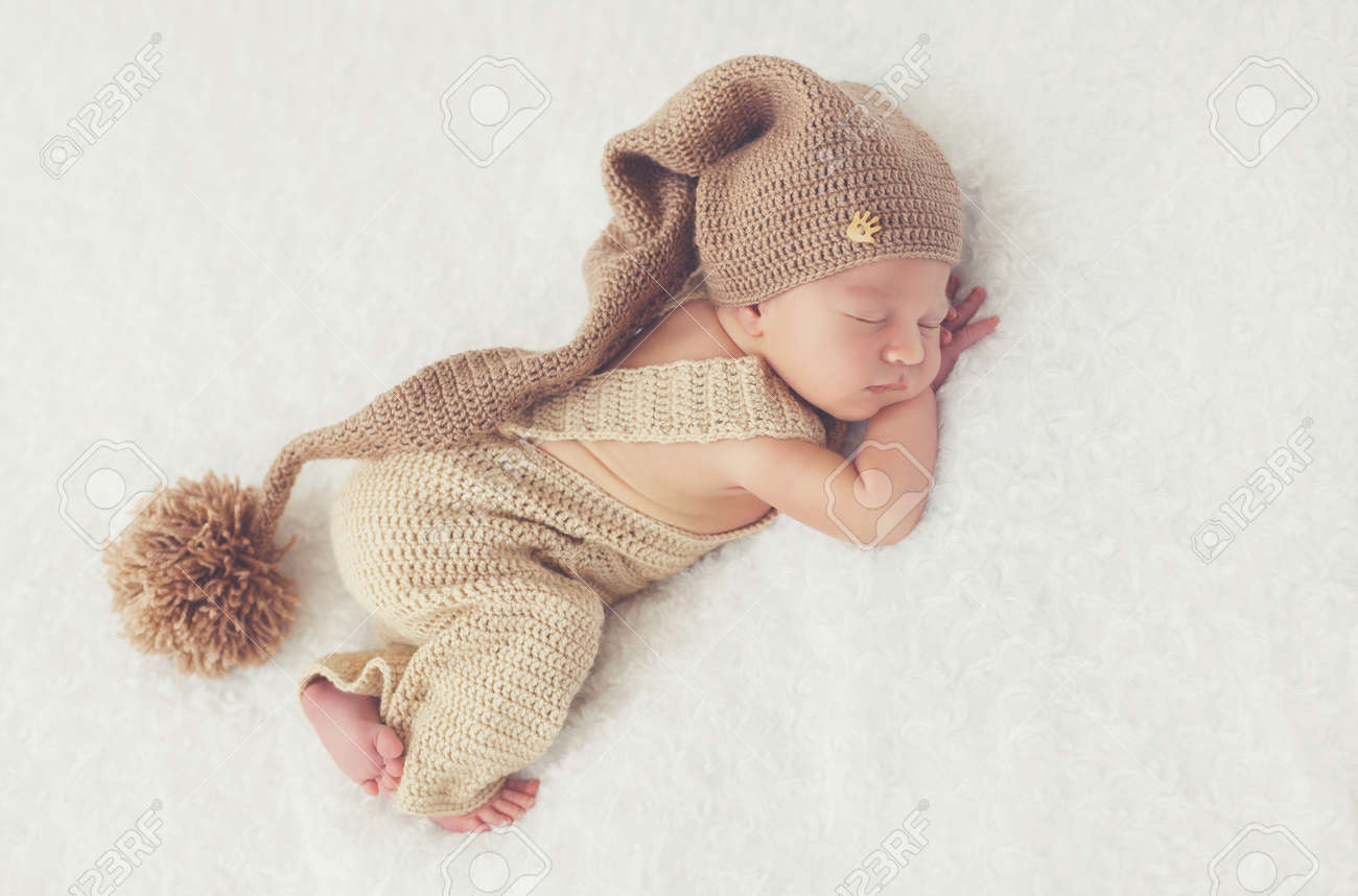 8f9791f4e59f Cute Newborn Baby In A Beige Knit Suit And A Brown Knitted Cap ...