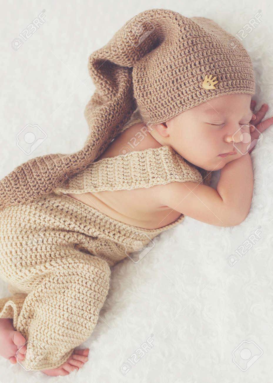 fc075a26cc00 Lindo bebé recién nacido en un traje de punto beige y un gorro de lana  marrón, doblada debajo de la cabeza y el mango apretando los pies,  dispuesto a ...