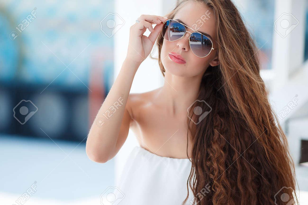 cbfc5c8f17 Joven Hermosa Mujer Morena Con Cabello Largo Castaño, Gafas De Sol, Lápiz  Labial Rosado, Mole Atractivo Cerca Del Labio Inferior, Vestido Con Un  Mameluco ...