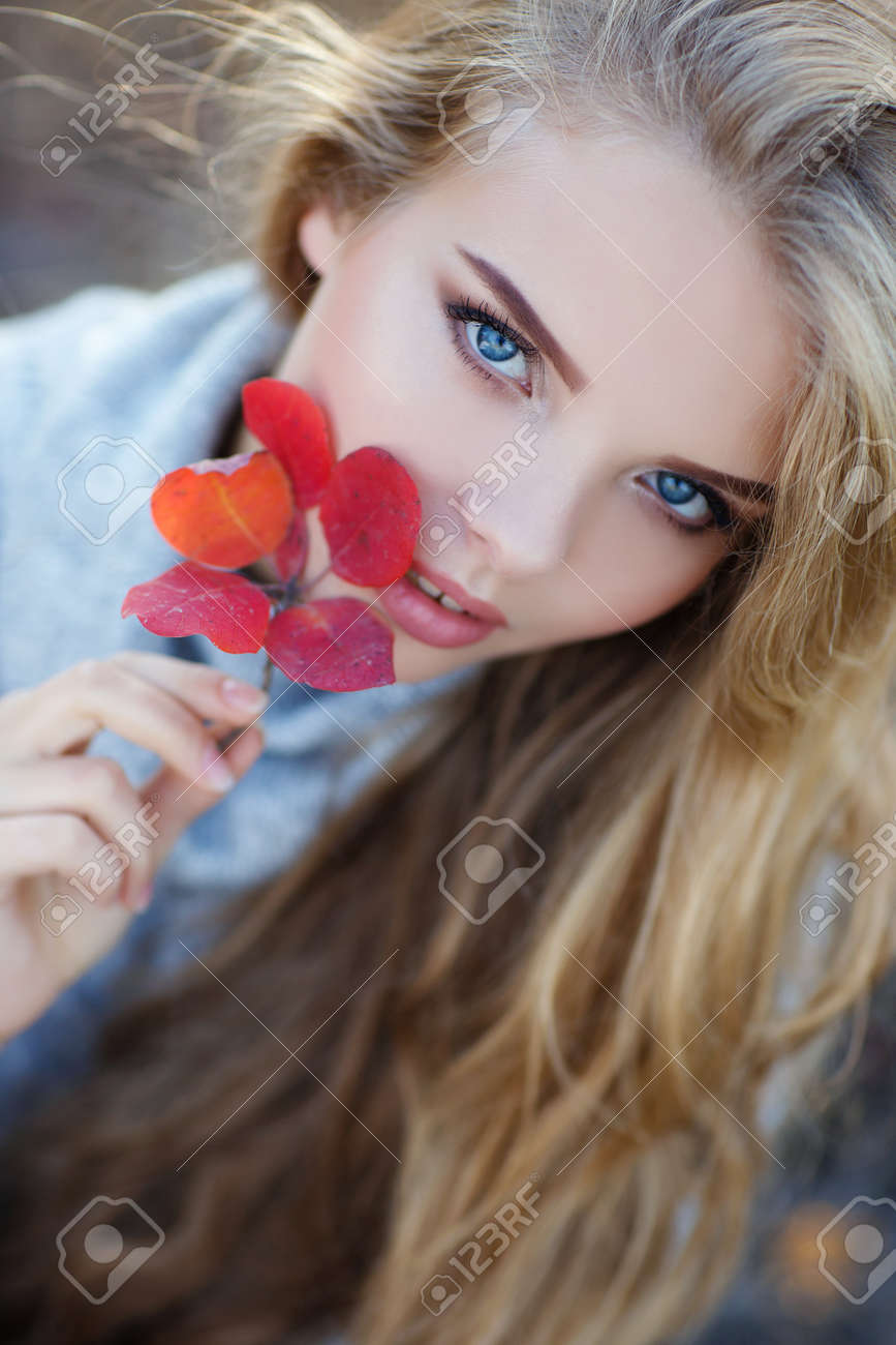 Autumn portrait of beautiful young woman with long blonde hair and blue eyes, dressed in gray-blue knitted sweater, light makeup, spends time alone outdoors ...