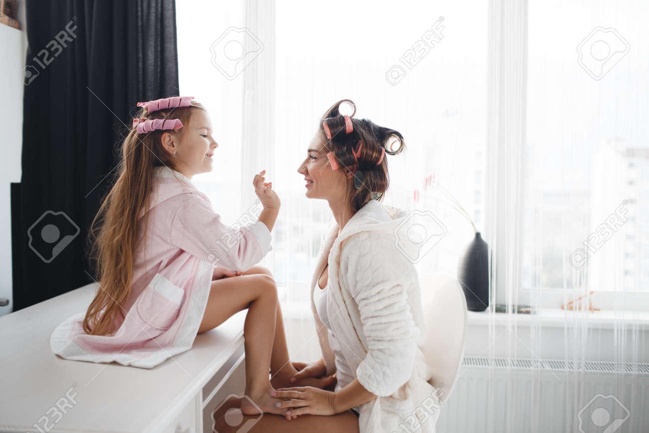 Faire Une Belle Chambre mère et sa jeune fille pour vous faire une belle coiffure, chambre blanche  près de la fenêtre, en aidant les uns les autres, le vent cheveux sur de