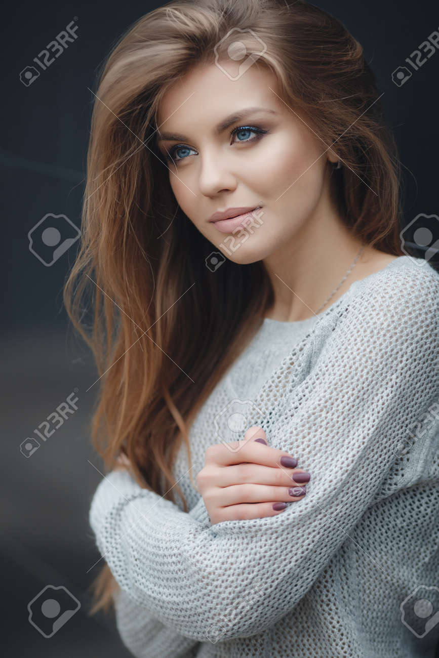 fb4eb6f1e6360 Young beautiful woman with long brown hair, light makeup and cute smile, wearing  a knitted pullover, light gray, posing alone, standing on a dark gray ...