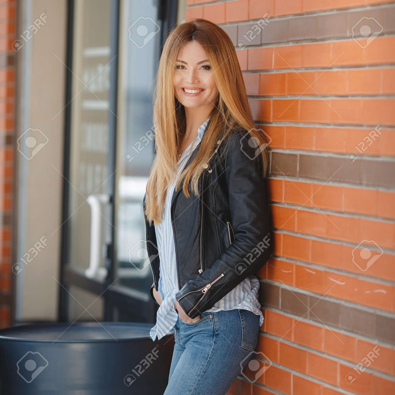 81bfa9a3aa648 A slender, tall, beautiful woman, model, long straight red hair, dressed in  a light striped shirt, blue jeans and a black leather jacket, ...