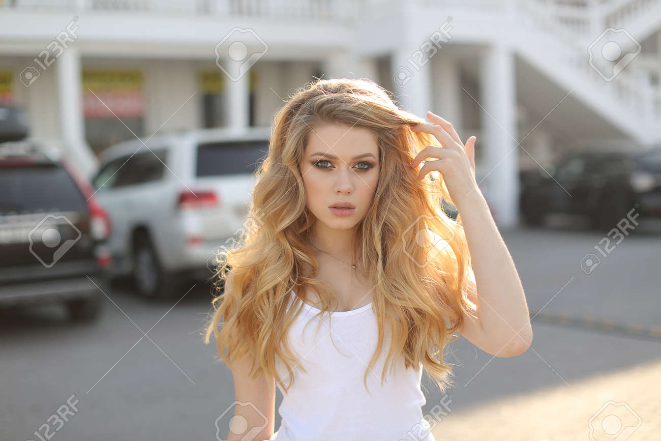 A Young Beautiful Woman With Long Wavy Hair And Green Eyes
