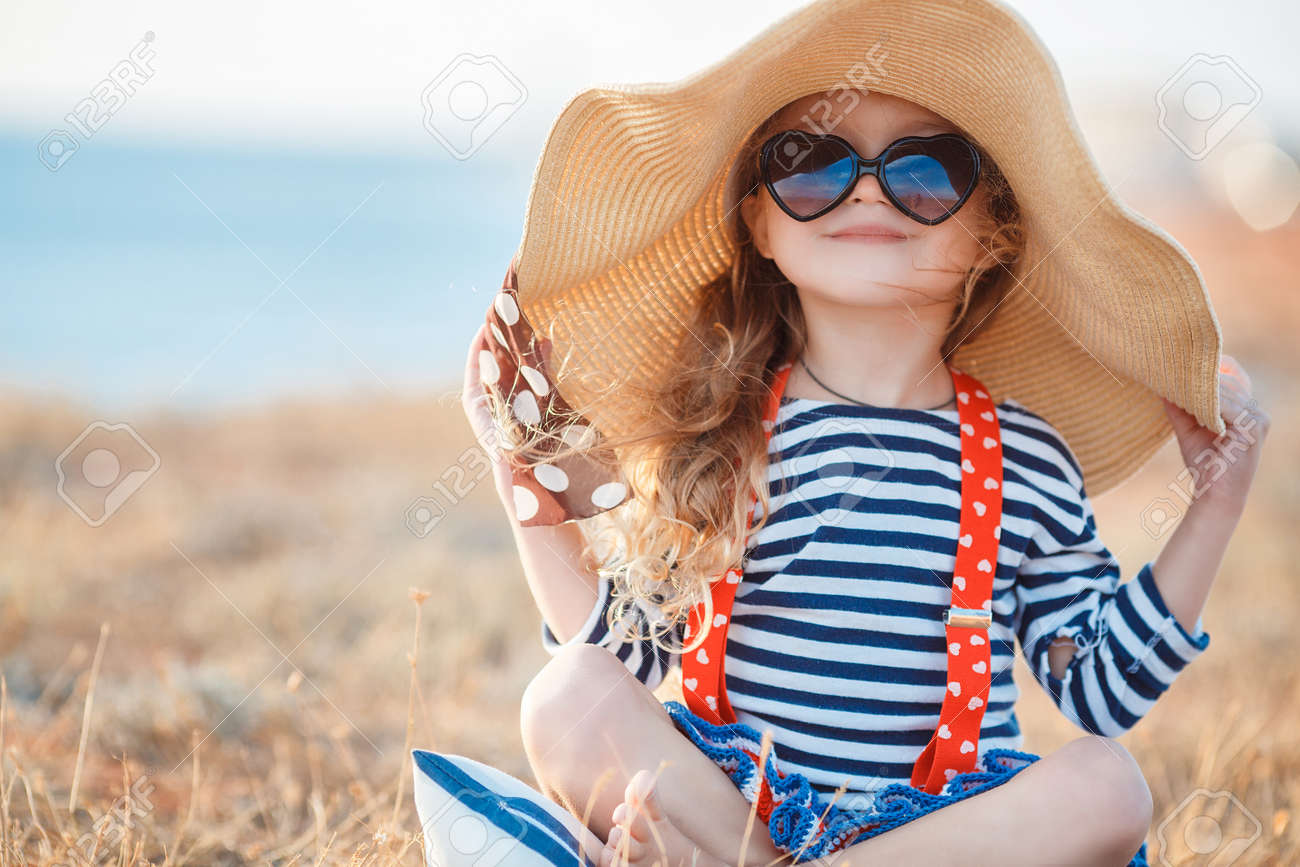 Happy little girl with long blond hair in a straw hat and sunglasses walks on a meadow at sunset with a seascape on the background. Ð¡hild plays alone in nature while sitting on dry grass near a pond. - 158410636
