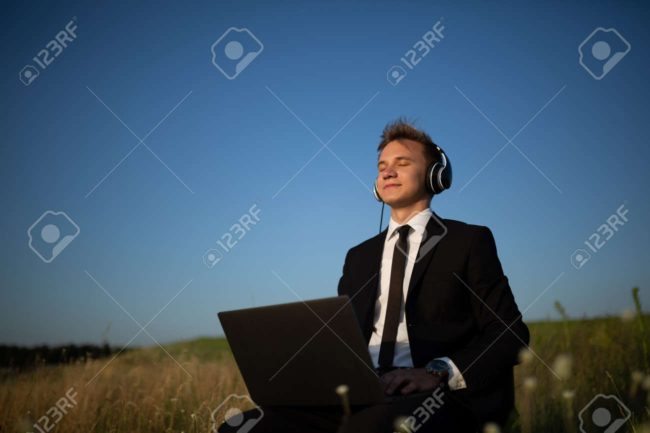 Young Happy Man With Headphones Listening Music In Field Laptop