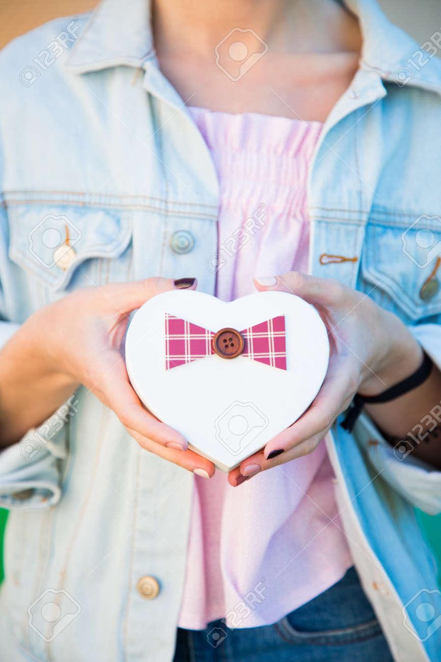 Banque d images - Mains féminines tenant la boîte-cadeau en forme de coeur  dans ses mains. Bannière romantique pour la Saint-Valentin. 49c5572a28de