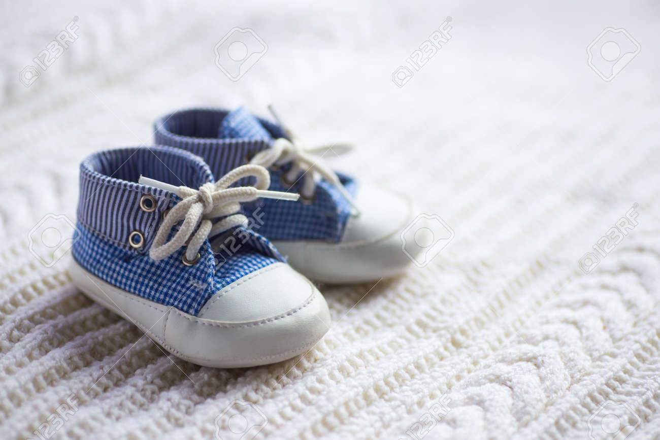 sold worldwide sold worldwide united states Cute Baby Boy Blue Sneakers On White Knitted Fabric. Concept ...