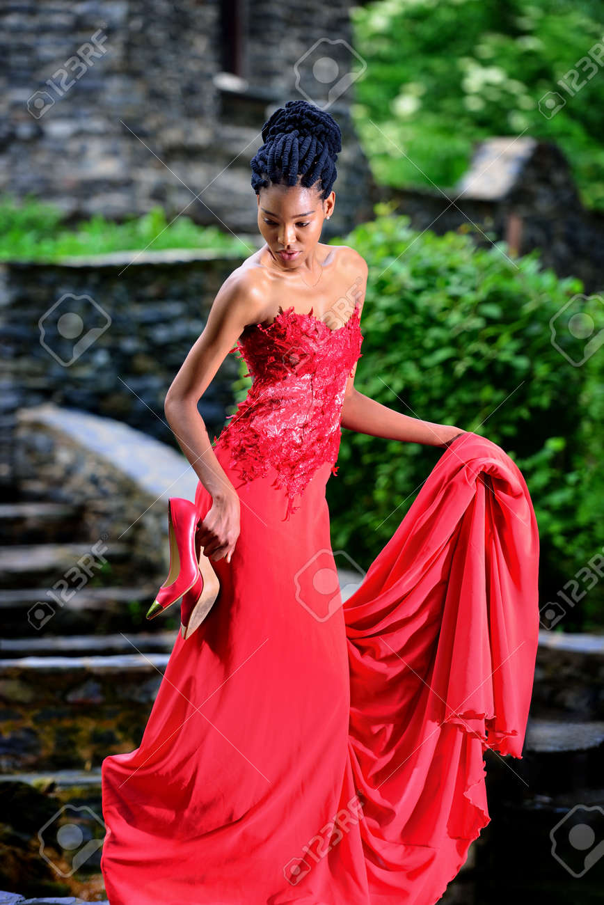 African American Girl In A Red Dress With Red Shoes In His Hand ...