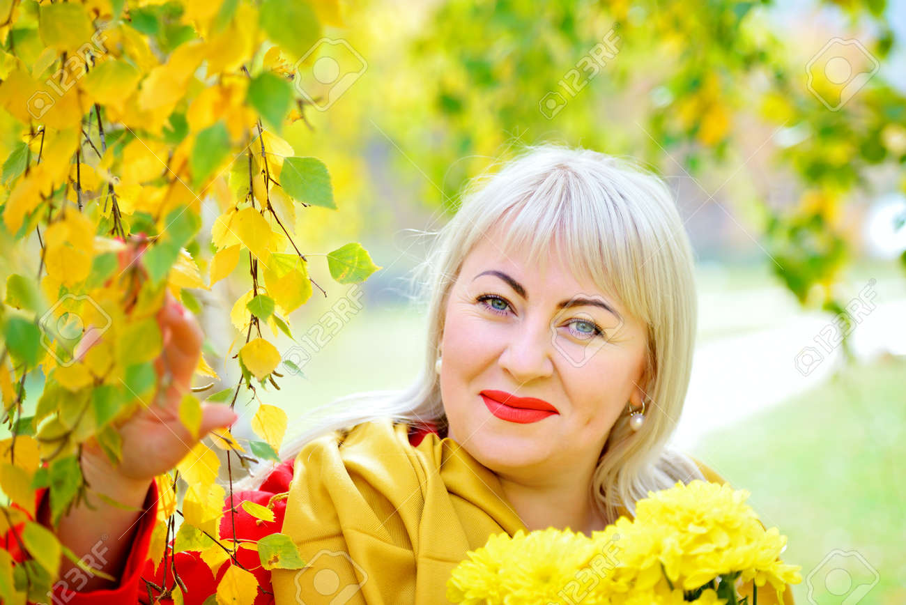 Fashionable portrait of blonde woman plus size outdoors. She stands in the autumn near a tree with yellow leaves in a red cloak, looking at the camera and smiling. Close-up. - 159011593