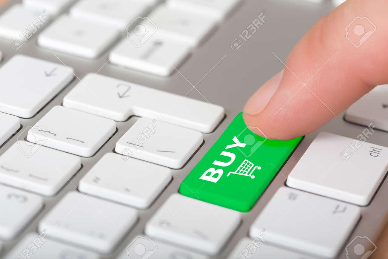 Masculino dedo de clic sobre el botón COMPRAR en el teclado del ordenador  con botones blancos, pero el botón de compras verde con el carro de símbolo