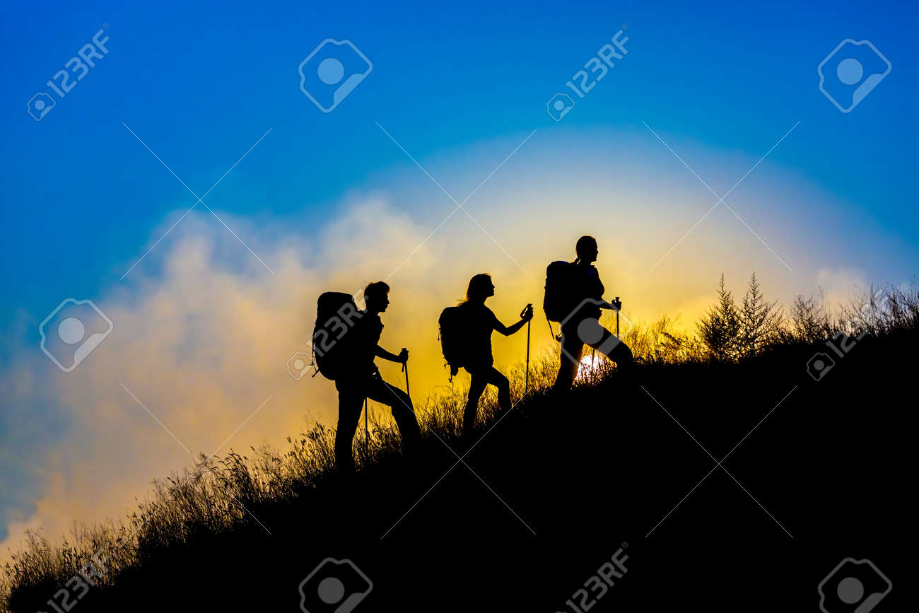Silhouettes of three people walking with backpacks and other hiking gear up toward top wild grass mountain mother father daughter bright luminous sunrise sky background - 47766590