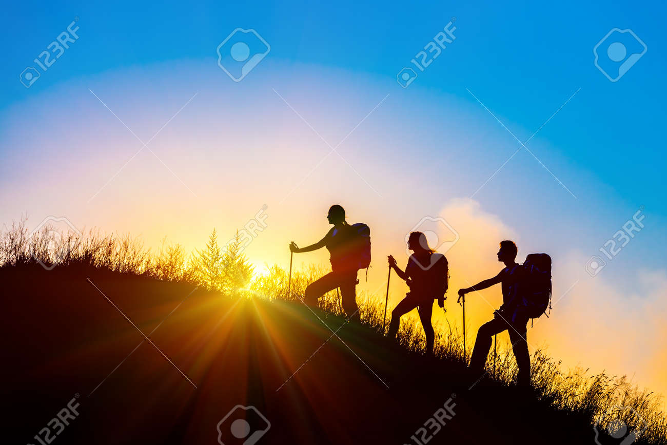 Group of people silhouettes walking toward mountain summit with backpacks hiking trekking gear meeting uprising sun sunbeams and blue sky of background - 47766591